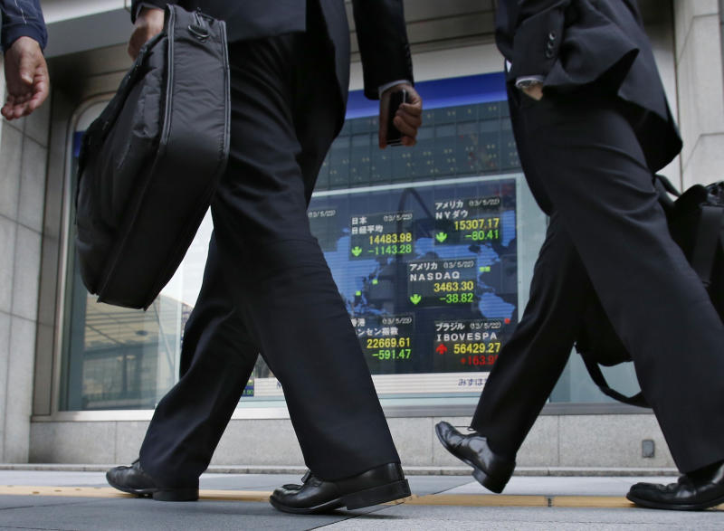 People walk by an electronic stock indicator outside a securities firm in Tokyo, Thursday, May 23, 2013. Japanese stocks plummeted Thursday after a spike in government bond yields and unexpectedly weak Chinese manufacturing spooked investors sitting atop months of massive gains in share prices. The Nikkei 225 in Tokyo nosedived 7.3 percent to close at 14,483.98, its worst drop since the 2011 earthquake disaster. (AP Photo/Shizuo Kambayashi)