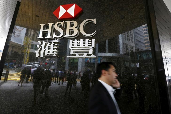 Man walks past a logo of HSBC outside a branch at the financial Central district in Hong Kong