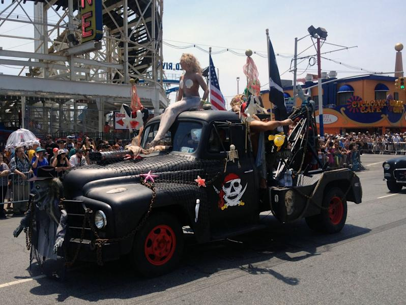 The Annual Coney Island Mermaid Parade proceeds along Surf Avenue as thousands of people mobbed the seaside amusement district, Saturday, June 22, 2013, in Brooklyn, New York. Coney Island was hit hard by Superstrom Sandy last October, but its boardwalk was one of the few on the coast that was spared, though organizers feared they would have to cancel the parade after their offices flooded last year. (AP Photo/Tess Domb Sadof)