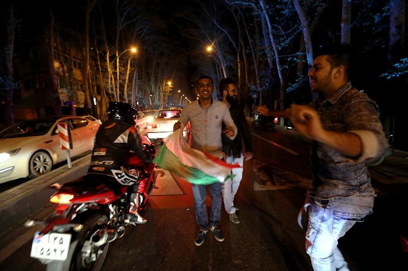 People dance and hold an Iranian flag as they celebrate on Valiasr street in northern Tehran on April 2, 2015, after the announcement of an agreement on Iran nuclear talks (AFP Photo/Atta Kenare)