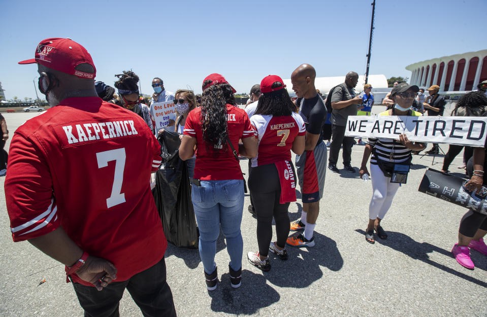 INGLEWOOD, CA-june 11, 2020: Katie Fuller, 74, of Inglewood, right, holding sign, joins other protesters in the Forum parking lot, across the street from Sofi Stadium in Inglewood, background, demanding that the NFL apologize to former NFL quarterback Colin Kaepernick. The protesters also took a knee for 8 minutes and 46 seconds to remember George Floyd who who held down by a police officer with a knee to his neck for the same time and died as a result. (Mel Melcon/Los Angeles Times via Getty Images)