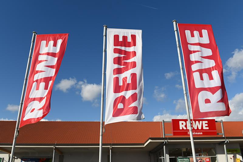25 February 2020, Hessen, Volkmarsen: Flags with the logo of the food retailer Rewe are waving in front of a branch. Photo: Uwe Zucchi/dpa (Photo by Uwe Zucchi/picture alliance via Getty Images)