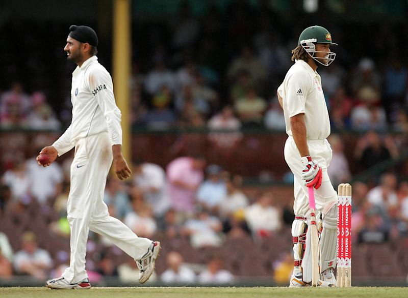 Harbhajan Singh walks past Andrew Symonds back to his bowling mark.