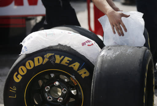 Crew members use ice to cool down tires for driver Greg Biffle during practice for Sunday's NASCAR Sprint Cup series auto race at Kansas Speedway in Kansas City, Kan., Friday, Oct. 4, 2013. (AP Photo/Orlin Wagner)
