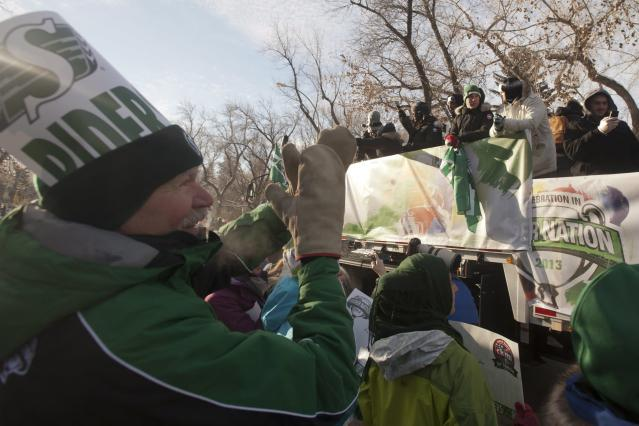 Jerry Zimmer cheers as the Saskatchewan Roughriders pass by on their float during the Grey Cup parade on Tuesday, Nov. 26, 2013 in Regina, Saskatchewan. The Roughriders defeated the Hamilton Tiger-Cats 45-23 in the 101st CFL Grey Cup on Sunday. (AP Photo/The Canadian Press, Liam Richards)