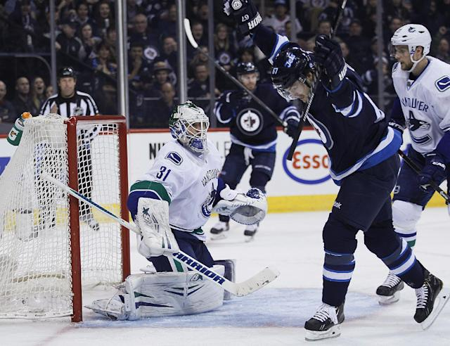 Winnipeg Jets' Michael Frolik (67) celebrates Andrew Ladd's goal on Vancouver Canucks goaltender Eddie Lack (31) as Canucks' Alexander Edler (23) watches during the second period of an NHL hockey game Wednesday, March 12, 2014, in Winnipeg, Manitoba. (AP Photo/The Canadian Press, John Woods)