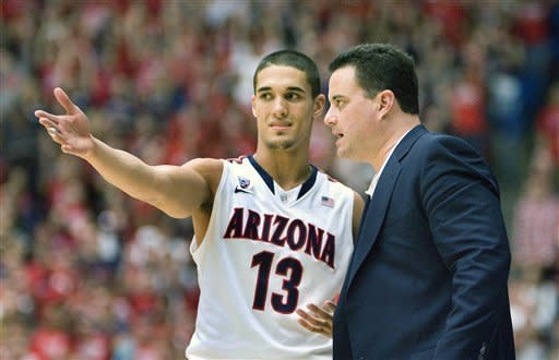 Arizona's head coach Sean Miller, right, talks with Nick Johnson (13) during the second half of an NCAA college basketball game against Southern California at McKale Center in Tucson, Ariz., Saturday, Jan. 26, 2013. (AP Photo/Wily Low)