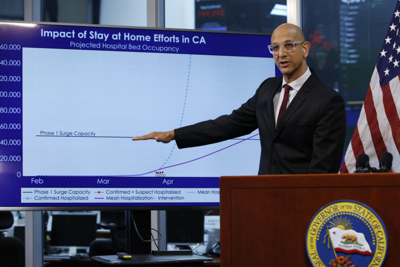 Dr. Mark Ghaly, secretary of the California Health and Human Services, gestures to a chart showing the impact of the mandatory stay-at-home orders during a news conference on the state's response to the coronavirus, at the Governor's Office of Emergency Services in Rancho Cordova, Calif. in Rancho Cordova, Calif., Wednesday, April 1, 2020. Gov. Gavin Newsom announced that California schools will likely remain closed for the rest of the school year, but provide off-site education due to coronavirus pandemic.(AP Photo/Rich Pedroncelli, POOL)