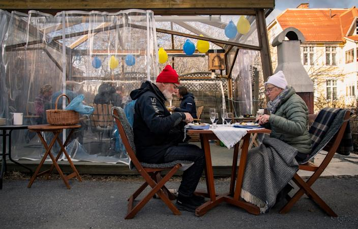 A senior couple eat dinner keeping distance from the rest of their family during the coronavirus pandemic on April 18, 2020 in Ostersund, Sweden.
