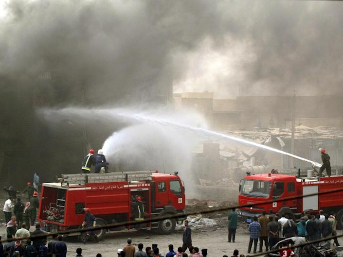<p>Iraqi firefighters tackle a burning building after the airstrike in Baghdad</p>Goran Tomasevic/Reuters