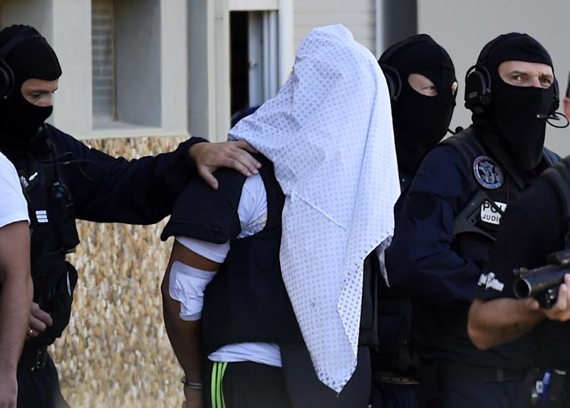 French police escort Yassin Salhi (C), a man suspected of decapitating his boss in an attack on a gas factory, as they leave his flat in Saint-Priest on June 28, 2015 (AFP Photo/Philippe Desmazes)