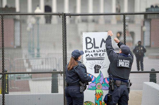 PHOTO: Capitol police remove a Black Lives Matter protest sign that was placed on the security fencing on the west side of the United States Capitol on on Jan. 8, 2021. (Jack Gruber/USA Today)