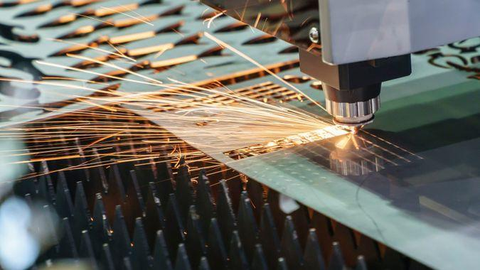 The fiber laser cutting machine cutting the sheet metal plate with the sparking light.