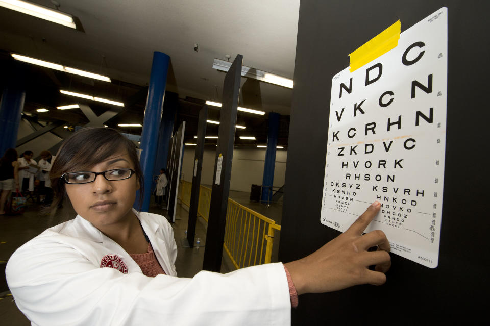 Optometry student Brenda Alcantar gives an eye test on the first day of the fourth annual free health clinic at the Los Angeles Sports Arena in downtown Los Angeles September 27, 2012.  The free clinic, organized by nonprofit Care Harbor, aims to provide medical, vision and dental care at no charge for thousands of needy residents over a four day period.  Health care is one of the top issues in the upcoming presidential election.  Some 49.9 million Americans, or 16.3 percent of the total US population, are uninsured, according to CNN.  AFP PHOTO / Robyn Beck        (Photo credit should read ROBYN BECK/AFP/GettyImages)