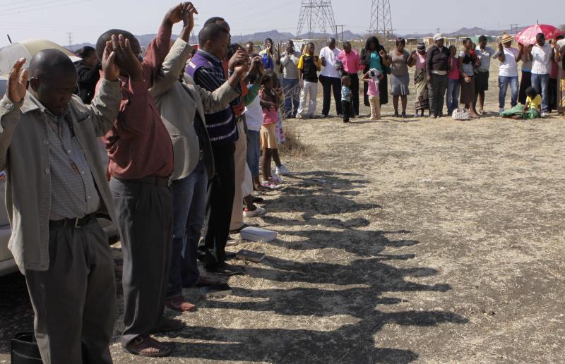 A group of churchgoers join hand in prayer at the site, Sunday Aug. 19, 2012 at the Lonmin platinum mine near Rustenburg, South Africa, during a memorial service for 34 dead striking miners who were shot and killed bt police last Thursday. Miners must return to work Monday or face being fired from the mine where rivalry between unions has exploded into violence. (AP Photo/Denis Farrell)