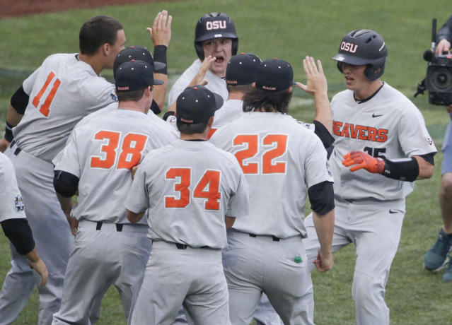 Oregon State's Adley Rutschman, right, is congratulated near the dugout after his solo home run against North Carolina during the first inning of an NCAA College World Series baseball elimination game in Omaha, Neb., Wednesday, June 20, 2018. (AP Photo/Nati Harnik)