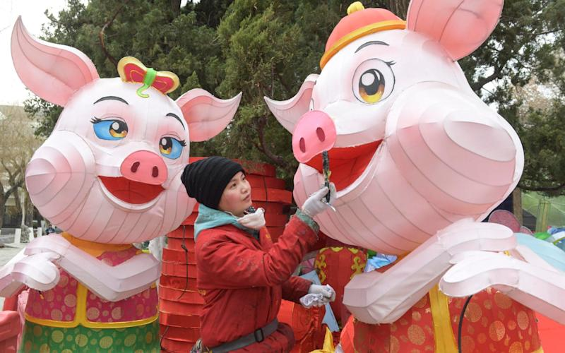 A craftswoman paints a lantern in the shape of a pig in Jinan, China, on January 9, 2019 - Visual China Group