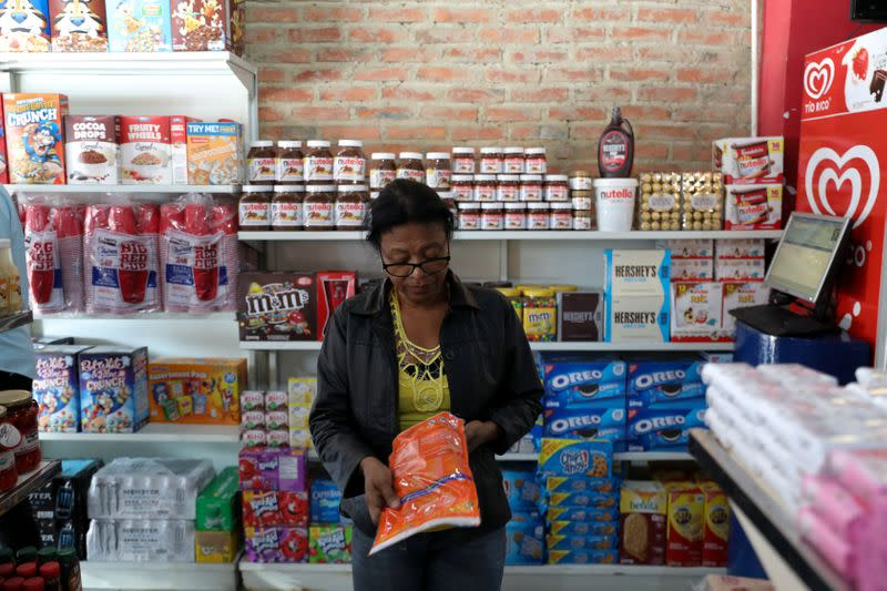 """A woman check prices of a detergent in the """"bodegon"""" named """"Mini Walmart"""" in Puerto Cabello"""