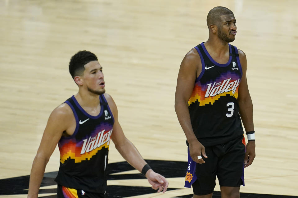 Phoenix Suns guard Devin Booker, left, and guard Chris Paul (3) walk on the court during the second half of Game 5 of basketball's NBA Finals against the Milwaukee Bucks, Saturday, July 17, 2021, in Phoenix. (AP Photo/Ross D. Franklin)