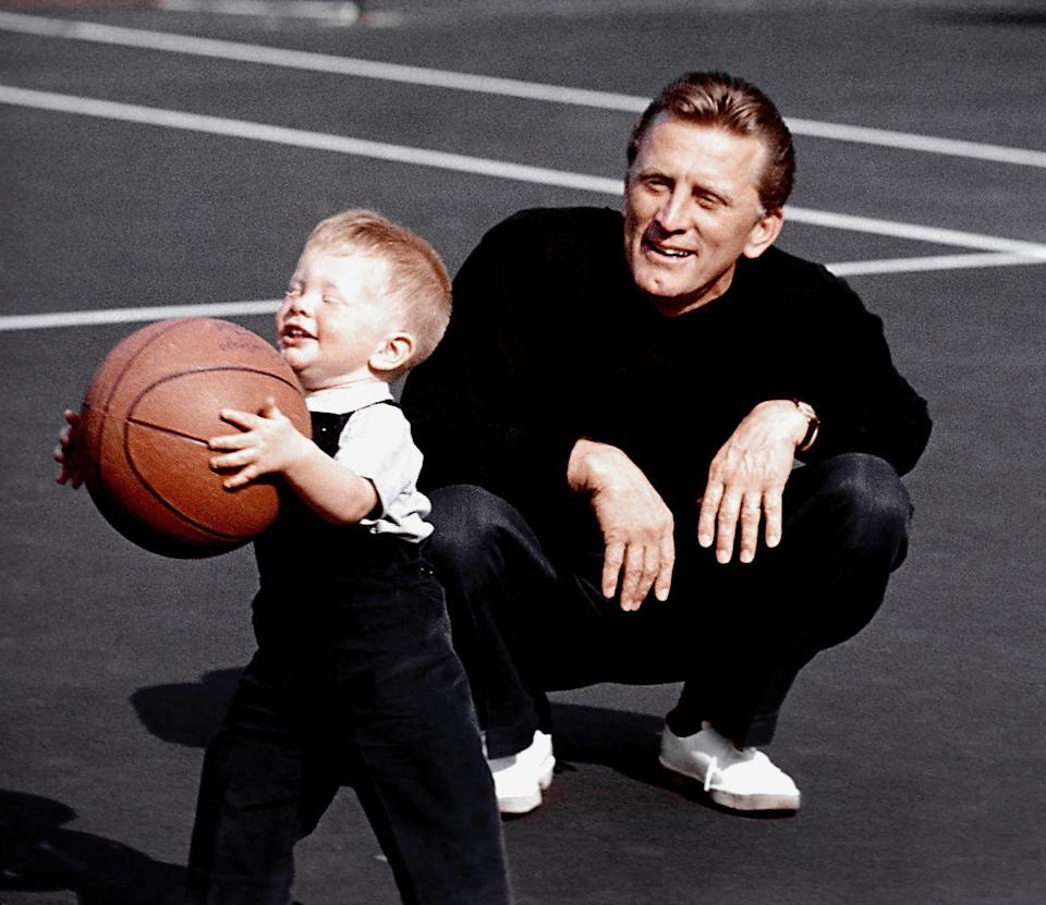<p>Kirk Douglas looks on as his son Peter Vincent Douglas handles a basketball at their Los Angles home in 1957. </p>