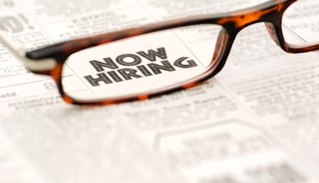 Now Hiring classified ad showing through reading glasses.