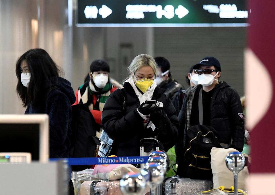 People wearing protective masks are seen at Malpensa airport near Milan, Italy, March 9, 2020. REUTERS/Flavio Lo Scalzo