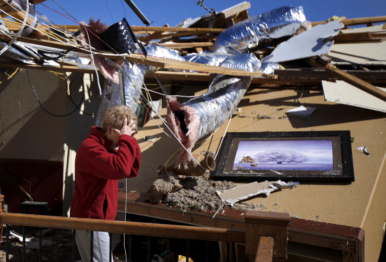 Carole Beckett reacts as she sorts through belongings at her home after a tornado moved through Woodward, Okla., Sunday, April 15, 2012.  Residents of several states scoured through the wreckage of battered homes and businesses after dozens of tornadoes blitzed the Midwest and Plains Saturday night. (AP Photo/The Oklahoman, Bryan Terry)