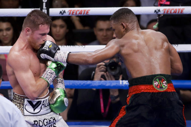 Canelo Alvarez, left, of Mexico, gets hit by Daniel Jacobs during a middleweight title boxing match Saturday, May 4, 2019, in Las Vegas. (AP Photo/Isaac Brekken)