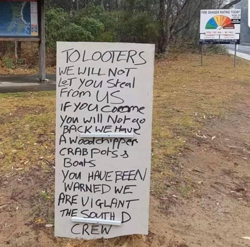 A sign sits in South Durras, on the NSW South Coast, warning would-be looters.