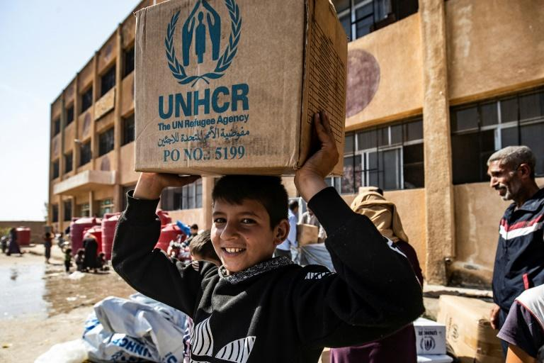 Displaced Syrians, who fled their homes in the border town of Ras al-Ain, receive humanitarian aid on October 12, 2019, in the town of Tal Tamr -- a UN resolution that would have extended aid for a year has been vetoed (AFP Photo/Delil SOULEIMAN)