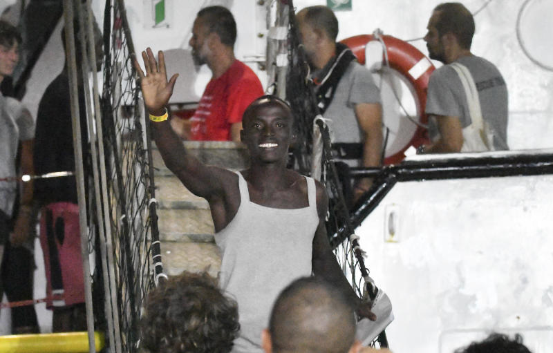 A man waves as he disembarks from the Open Arms rescue ship on the Sicilian island of Lampedusa, southern Italy, Tuesday, Aug. 20, 2019. An Italian prosecutor ordered the seizure of a rescue ship and the immediate evacuation of more than 80 migrants still aboard, capping a drama Tuesday that saw 15 people jump overboard in a desperate bid to escape deteriorating conditions on the vessel and Spain dispatch a naval ship to try to resolve the crisis. (AP Photo/Salvatore Cavalli)
