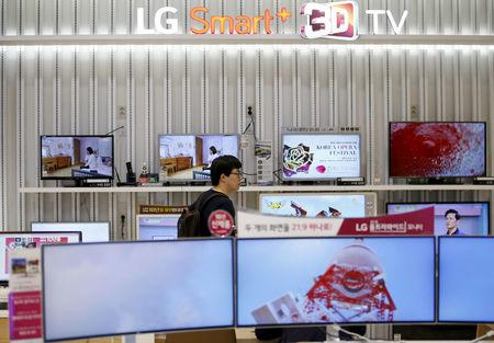 FILE PHOTO: A man looks at LG Electronics' TV sets, which are made with LG Display flat screens, at its store in Seoul