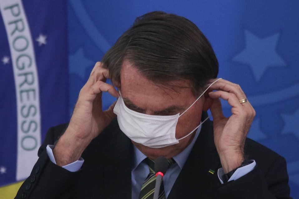 BRASILIA, BRAZIL - MARCH 18:  President of Brazil Jair Bolsonaro adjusts his protective mask during a press conference regarding government plans and measures on the Coronavirus (COVID-19) Outbreak in Brazil, at the Planalto Palace on March 18, 2020 in Brasilia, Brazil. (Photo by Andre Coelho/Getty Images)