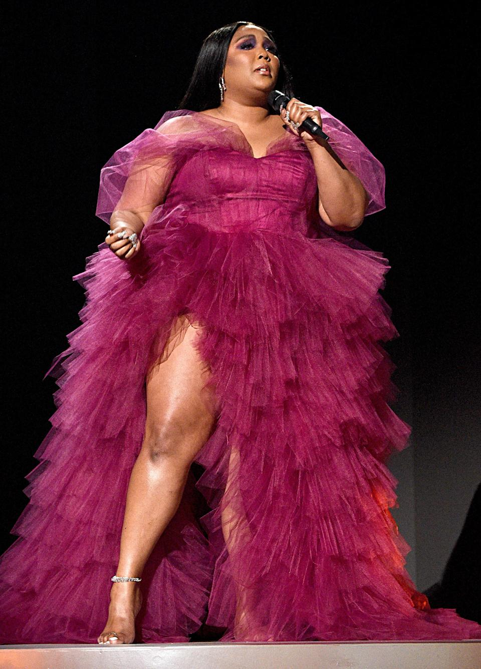 Lizzo looked like a dream when she took over the AMA stage in this plum gown with a thigh-slit courtesy of Dauxilly.