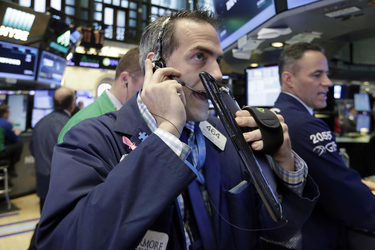 Trader Gregory Rowe, center, works on the floor of the New York Stock Exchange, Tuesday, June 27, 2017. Stocks are opening slightly lower on Wall Street, led by declines in phone and technology companies. (AP Photo/Richard Drew)