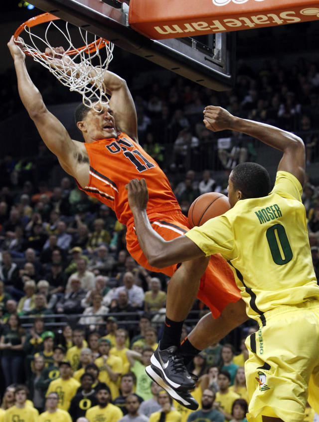 Oregon State's Malcolm Duvivier, left, slams a dunk over Oregon's Mike Moser during the second half of an NCAA college basketball game in Eugene, Ore., Sunday, Feb. 16, 2014. (AP Photo/Chris Pietsch)