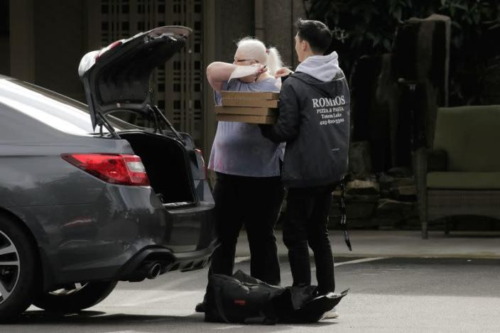 A worker coughs into her arm as she accepts pizza from a delivery driver at the Life Care Center of Kirkland, where two of three confirmed coronavirus cases in the state had links to the long-term care facility in Kirkland