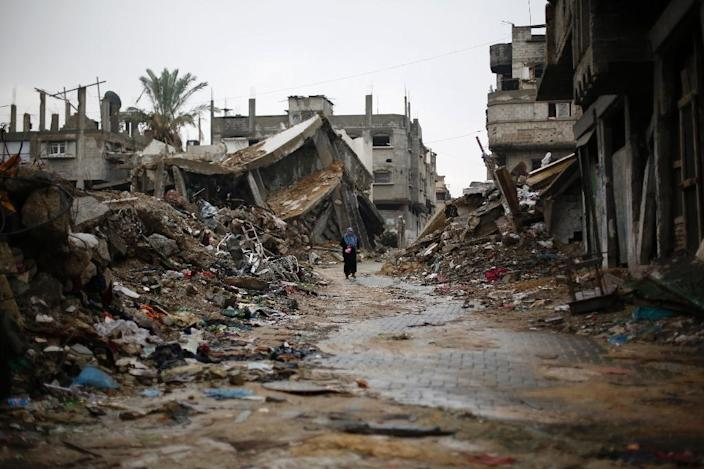 A Palestinian woman walks past houses that were destroyed during the 50-day Gaza war between Israel and Hamas-led militants, on November 24, 2014, in Gaza City (AFP Photo/Mohammed Abed)