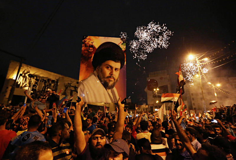 In this Monday, May 14, 2018 file photo, supporters of Shiite cleric Muqtada al-Sadr, carry his image as they celebrate in Tahrir Square, Baghdad, Iraq. The unexpected alliance between Iraq's mercurial Shiite cleric Muqtada al-Sadr and an Iran-backed coalition of powerful Shiite militias, who fought Islamic State group, will boost Tehran interests in Iraq and give it more leverage over the process of forming the next government. (AP Photo/Hadi Mizban, File)