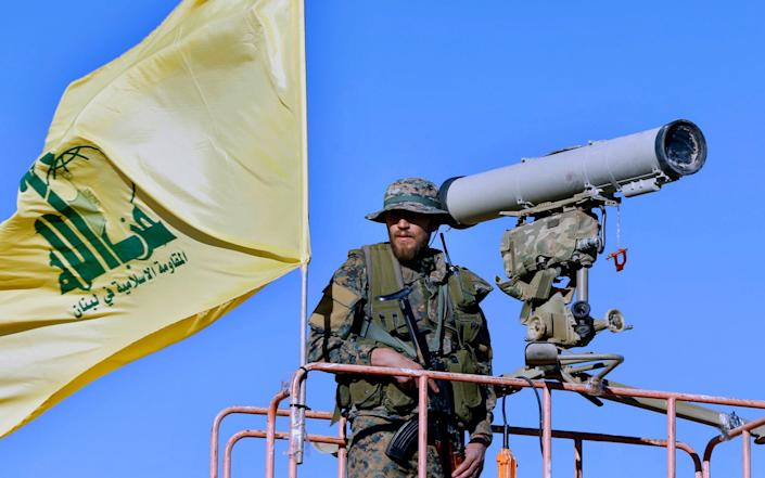 Hezbollah fighter stands at a watchtower at the site where clashes erupted between Hezbollah and al-Qaida-linked fighters