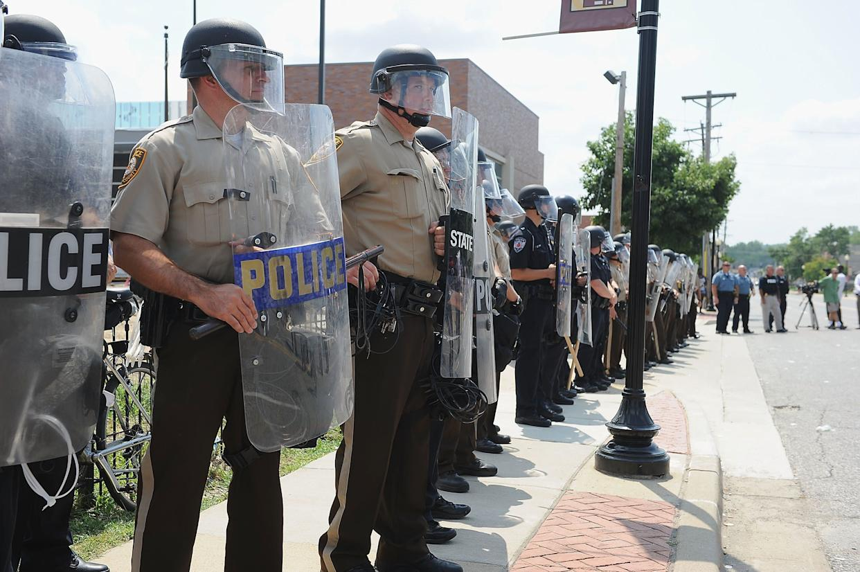FERGUSON, MO - AUGUST 11: St. Louis County Law Enforcement Officers stand in riot gear during a protest of the shooting death of 18-year-old Michael Brown by a Ferguson police officer, outside Ferguson Police Department Headquarters August 11, 2014 in Ferguson, Missouri. Civil unrest broke out as a result of the shooting of the unarmed black man as crowds looted and burned stores, vandalized vehicles and taunted police officers. Dozens were arrested for various infractions including assault, burglary and theft. (Photo by Michael B. Thomas/Getty Images)