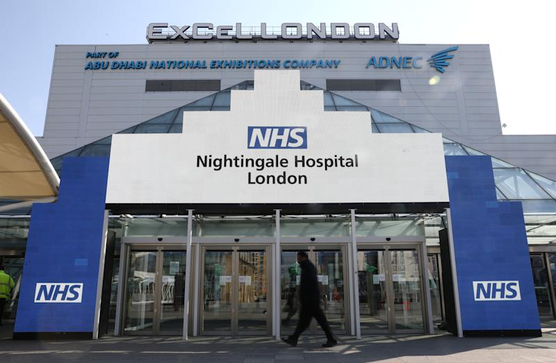A man walks outside the Excel Centre, London while it is being prepared to become the NHS Nightingale hospital as the spread of the coronavirus disease (COVID-19) continues, in East London, Britain, March 27, 2020. REUTERS/Simon Dawson