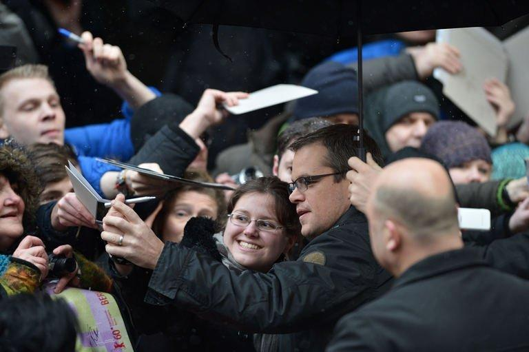 """US actor Matt Damon (C) poses for fans as he arrives at a press conference to present Gus van Sant's film """"Promised Land"""" part of the competition in the 63rd Berlinale Film Festival on February 8, 2013. Damon, who co-wrote the script and stars in the picture, said he was bewildered by critics who found the story of a natural gas executive wrestling with his conscience implausible and incoherent"""