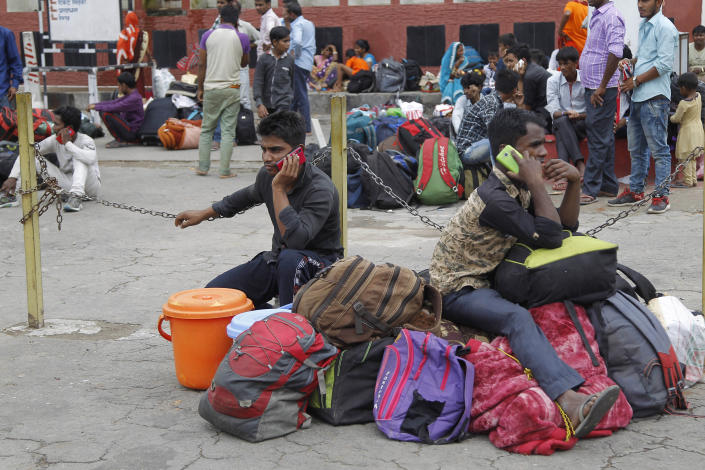 Indian migrant laborers speak on their mobile phones as they prepare to leave the region, at a railway station in Jammu, India, Wednesday, Aug. 7, 2019. Indian lawmakers passed a bill Tuesday that strips statehood from the Indian-administered portion of Muslim-majority Kashmir, which remains under an indefinite security lockdown, actions that archrival Pakistan warned could lead to war. (AP Photo/Channi Anand)