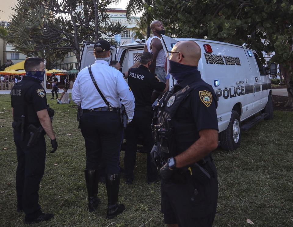An unidentified man is detained and later arrested on Sunday, March 21, 2021, at 5th Street and Ocean Drive while crowds of Miami Beach spring-breakers walk Ocean Drive several hours prior to a city-wide curfew that was put into effect after several nights of mass arrests. An 8 p.m. curfew has been extended in Miami Beach after law enforcement worked to contain unruly crowds of spring break tourists (Carl Juste/Miami Herald via AP)