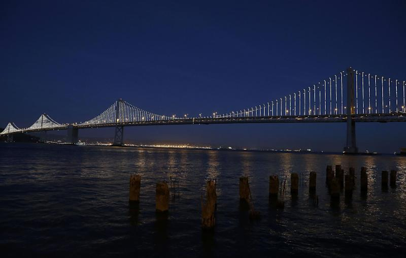 In this Wednesday, Feb. 20, 2013, photo,lights are turned on along the western half of the San Francisco-Oakland Bay Bridge on Pier 14 in San Francisco. The San Francisco-Oakland Bay Bridge has been turned into the latest, and by far the biggest, backdrop for New York artist Leo Villareal, who has individually programmed 25,000 white lights spaced a foot apart on 300 of the span's vertical cables to create what is being billed as the world's largest illuminated sculpture. (AP Photo/Jeff Chiu)