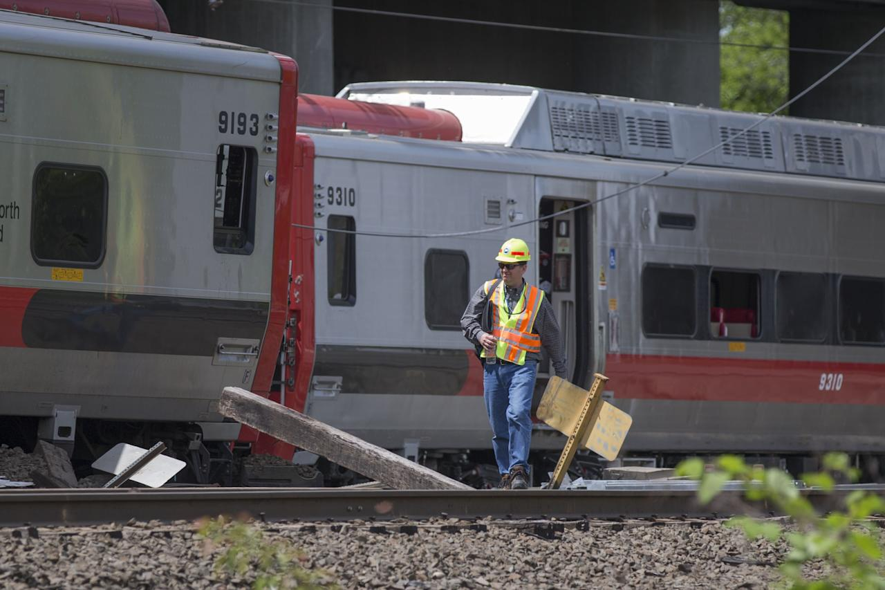 FAIRFIELD, CT - MAY 18: A Connecticut state investigator examines the scene of a Metro North train collision on May 18, 2013 in Fairfield, Connecticut. Two New Haven Line Metro North commuter trains collided on Friday, May 17 near Bridgeport, CT, injuring as many as 70 people.  (Photo by Michael Graae/Getty Images)