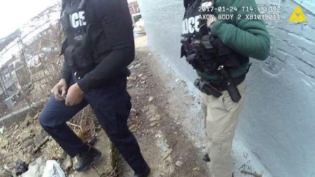 A still image captured from police body camera video appears to show two Baltimore police officers look on as a colleague places a small plastic bag in a trash-strewn yard (not shown) according to the Maryland Office of the Public Defender in this image released in Baltimore, Maryland, U.S. on July 19, 2017.    Courtesy Baltimore Police Department/Handout via REUTERS   ATTENTION EDITORS - THIS IMAGE WAS PROVIDED BY A THIRD PARTY. - RTX3C930
