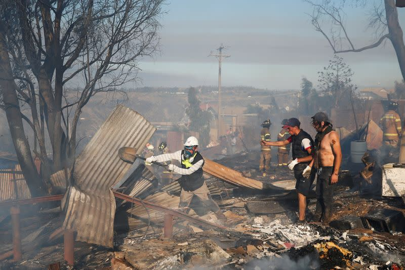 People help firefighters as they work to extinguish a fire in Valparaiso
