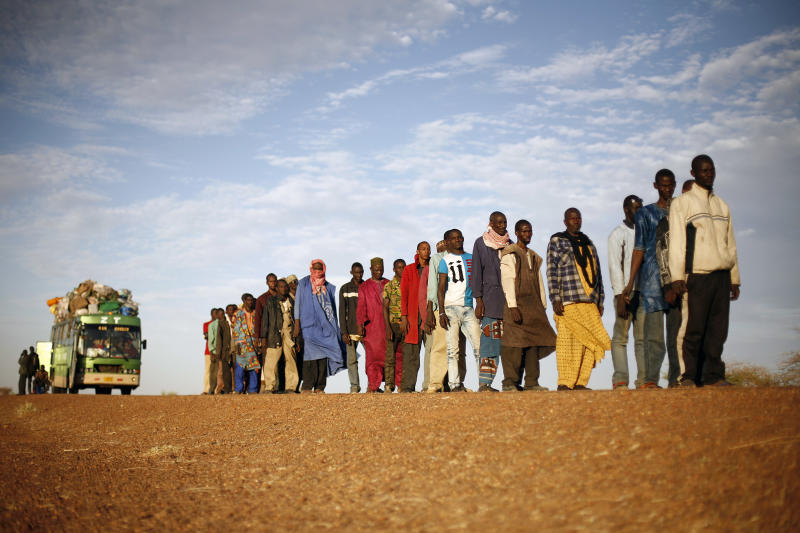 Travelers driving from Niamey, Niger, line up to be searched at the entrance of Gao, northern Mali, Tuesday, Feb. 12, 2013. Soldiers from Niger and Mali patrolled downtown Gao on foot Tuesday, combing the sand footpaths through empty market stalls to prevent radical Islamic fighters from returning to this embattled city in northern Mali. (AP Photo/Jerome Delay)